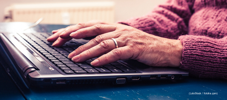 alte Frau arbeitet am Laptop