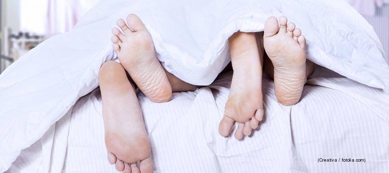zwei Paar Füße ragen aus Bett