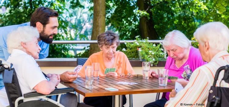 Gruppe von Seniorinnen spielt Karten.