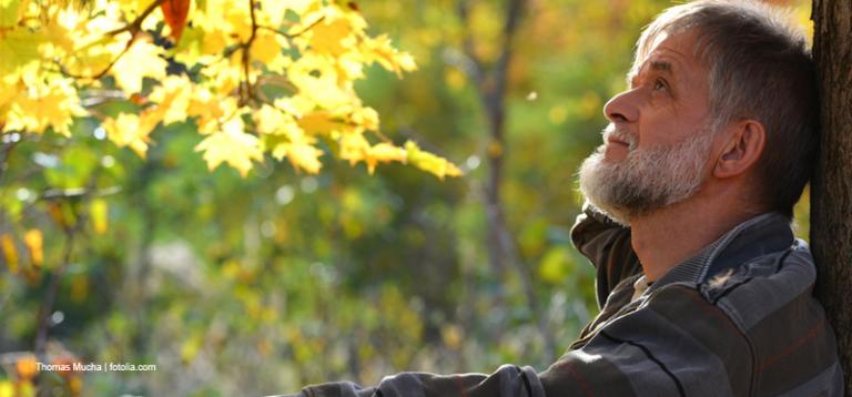 älterer Mann lehnt an Baum