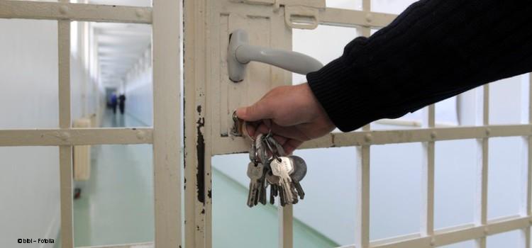 Beamter mit Schlüsselbund an Gefängnistür