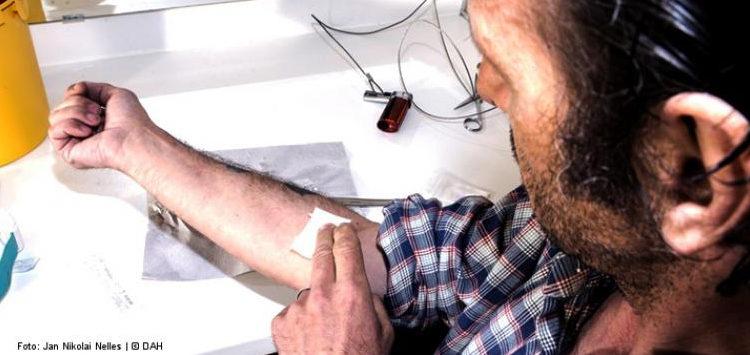 Mann drückt Tupfer auf Armbeuge