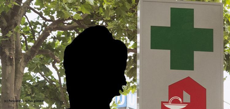 Eine anonyme Person vor einem Apotheken-Schild
