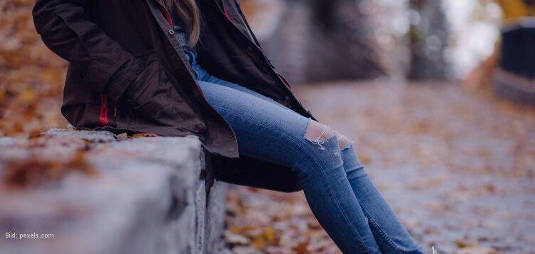 Sitzende Frau in Herbstlandschaft