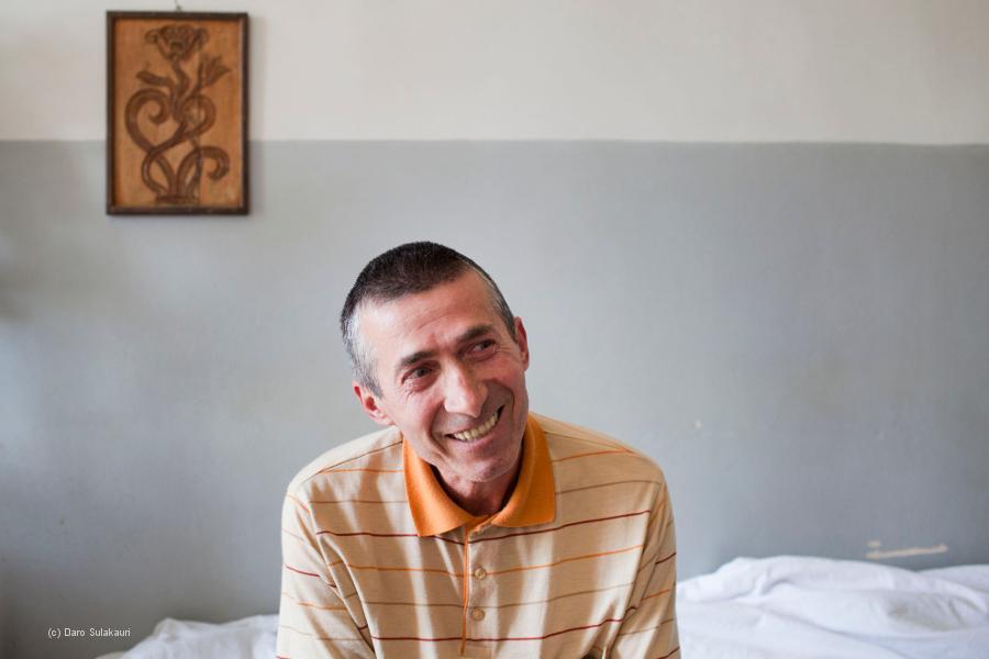 Ein Patient sitzt auf seinem Krankenhausbett.