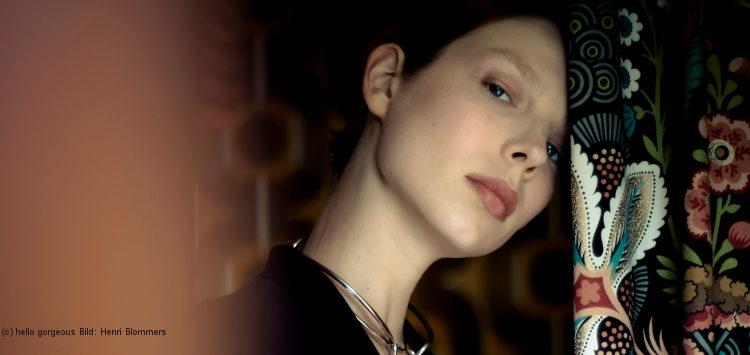 Porträt von Valentijn, die vor einem bunten Vorhang steht