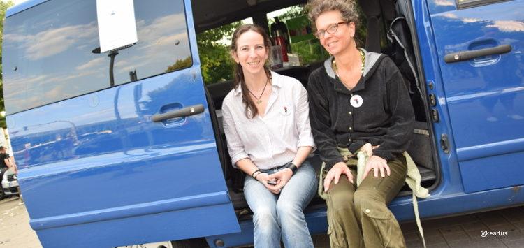 Zwei Beraterinnen sitzen vor dem blauen Bus des Projektes