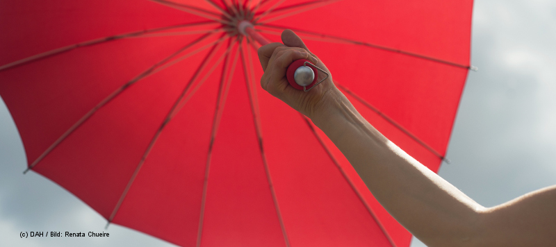 Ein Arm hält einen roten Regenschirm in die Höhe