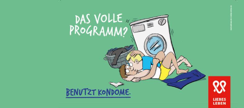 Zwei Männer liegen in enger Umarmung vor einer Waschmaschine. Darüber steht der Spruch: Das volle Programm? Benutzt Kondome!