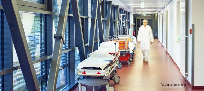 Flur im Krankenhaus mit zwei Betten und geschlossener Tür zur Ambulanz mit Arzt unscharf
