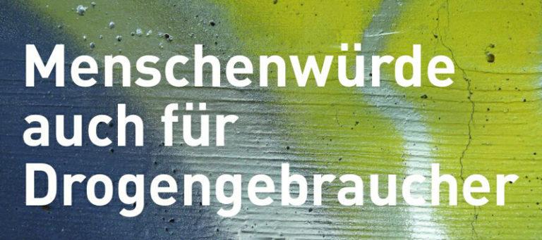 """Eine bunt besprühte Wand, davor der Slogan """"Menschenwürde auch für Drogengebraucher"""""""