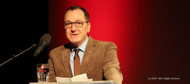 Das Bild zeigt DAH-Vorstandsmitglied Manuel Izdebski, der sich im Interview gegen Rechtspopulismus positioniert, hinter einem Rednerpult