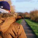 Auf dem Bild ist ein Mann in einem braunen Anorak von hinten zu sehen, der einen Weg in herbstlicher Umgebung lang geht.
