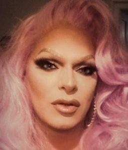 Stark geschminkte Dragqueen mit rosa Haaren