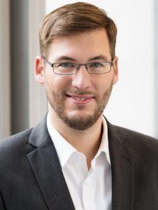 Junger Mann mit Brille, der weißes Hemd und schwarzes Jackett trägt