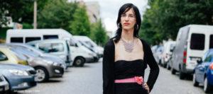 Frau mit Brille, roten Lippen, dunklen Haaren und schwarzem Minikleid steht mitten auf einer Straße, selbstbewusster Blick, links und rechts parkende Autos