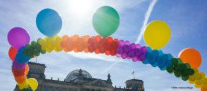 Eine Kette aus Luftballons in den Farben des Regenbogens vor dem Reichstagsgebäude