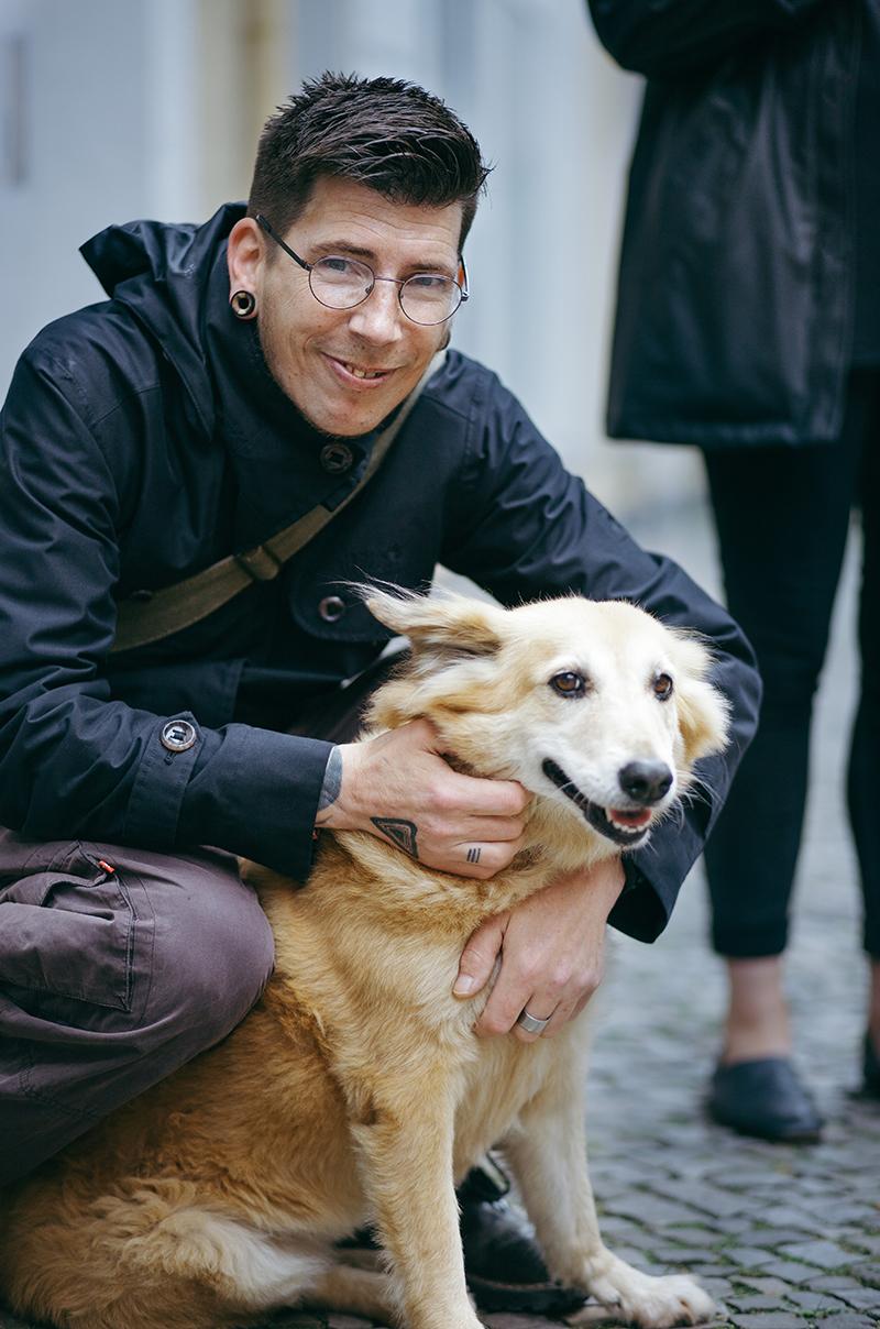 Bernd, Hundebesitzer, hält seinen Hund Jumper im Arm und lächelt. Jumper hat helles Fell.