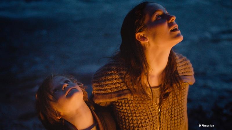Frau mit langen dunklen Haaren hat ihren Arm um einen Jungen gelegt, beide schauen nach oben, es ist dunkel, auf ihren Gesichtern ein heller Lichtschein