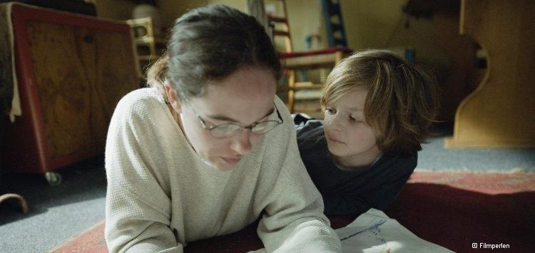 Frau mit langen, dunklen Haaren und Brille liegt bäuchlings auf dem Boden und liest in einer Zeitung; neben ihr ein Junge mit mittelbraunen Haaren