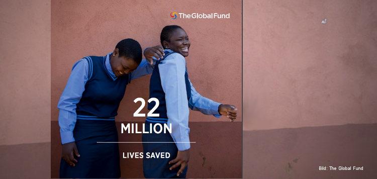 """Zwei lachende Mädchen in Schuluniform stehen vor einer braunen Wand, davor der Text """"22 million lives saved"""", oben das Logo des Global Fund."""