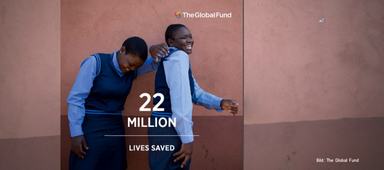 "Zwei lachende Mädchen in Schuluniform stehen vor einer braunen Wand, davor der Text ""22 million lives saved"", oben das Logo des Global Fund."