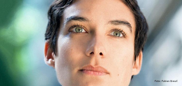 Das Gesicht einer jungen Frau mit kurzen dunklen Haaren, die nach oben blickt