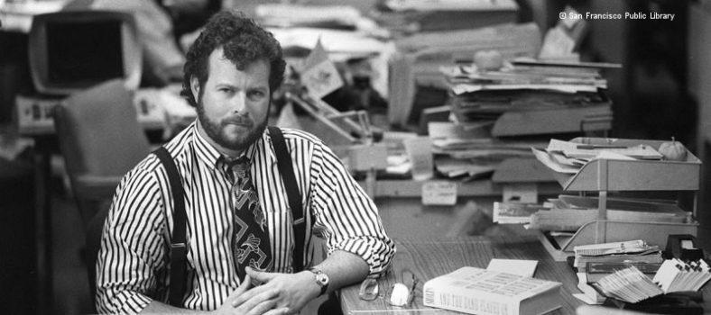 Schwarz-weiß-Foto von Randy Shilts: Mann mit Krawatte, Hemd und Hosenträgern sitzt an einem mit Büchern und Papier beladenen Schreibtisch