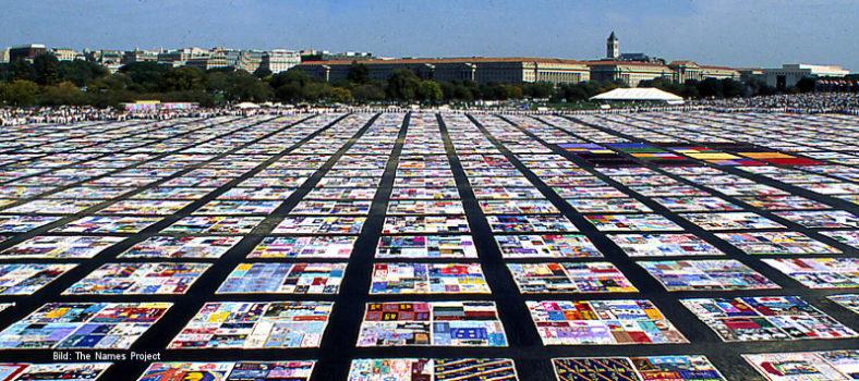 Eine große Masse ausgebreiteter bunter Tücher, die AIDS Memorial Quilt genannt werden und an Menschen erinnern, die an Aids gestorben sind