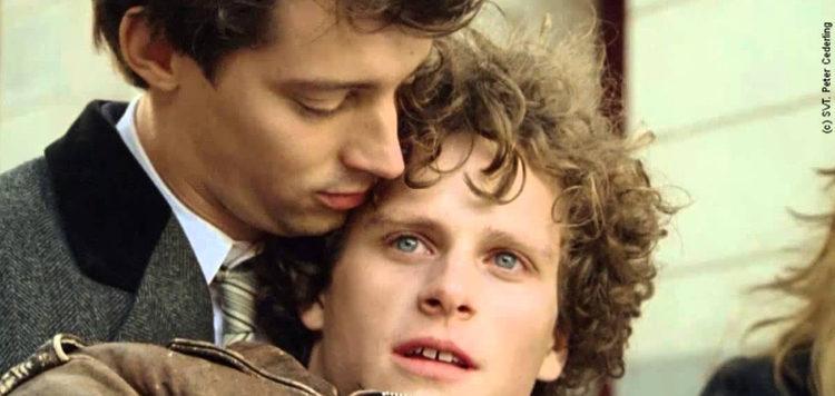 Zwei junge Männer, der eine hält den anderen in den Armen.