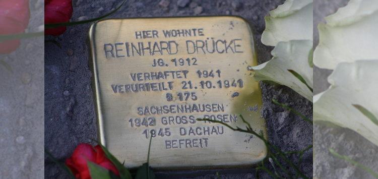 """Ein Stolperstein im Straßenpflaster, mit dem Text """"Hier wohnte Reinhard Drücke."""""""