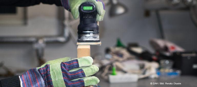 Person trägt Arbeitshandschuhe und schleift mit einem Werkzeug ein Holzteil