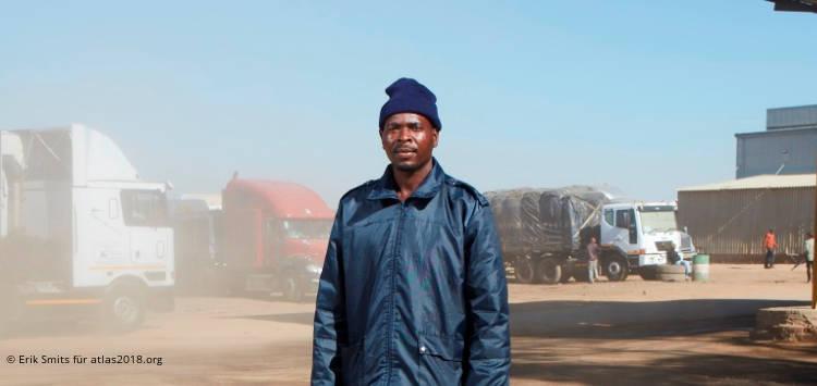 Afrikanischer Mann in blauer Jacke vor LKWs