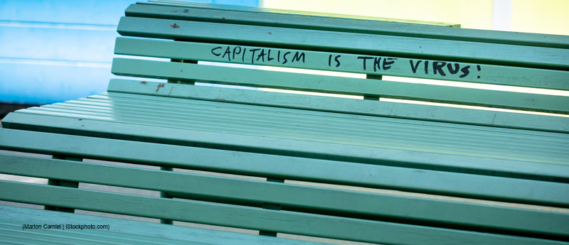 protest message against capitalism and the corona virus is written on a bench. outdoors